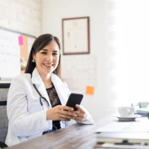 Doctor sitting at desk with cell phone in hand