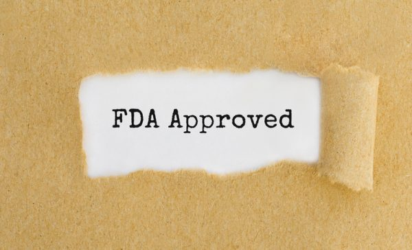 Text FDA Approved appearing behind ripped brown paper.