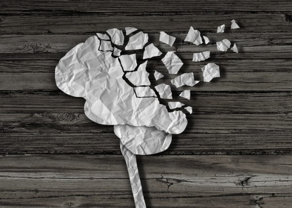 Dementia or brain damage and injury as a mental health and neurology medical symbol with a thinking human organ made of crumpled paper torn in pieces as a creative concept for alzheimer disease.