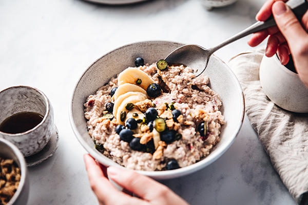 Woman eating oatmeal with fruit