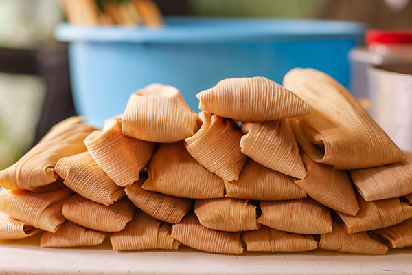 Delicious traditional Mexican tamales piled on a table