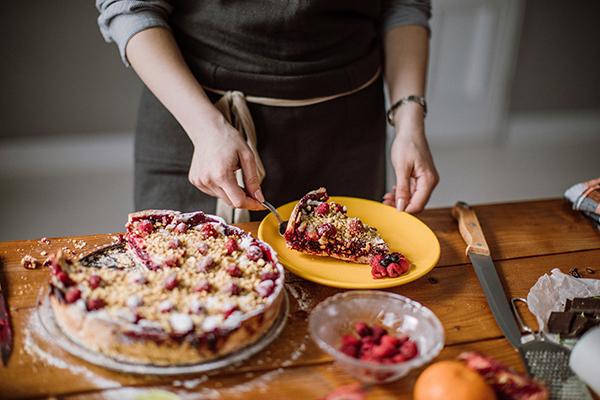 Woman cutting a slice out of a berry pie