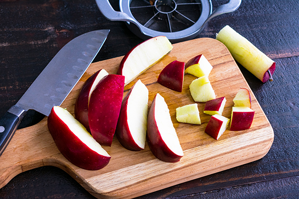 Slicing a red apple into chunks on a wood cutting board