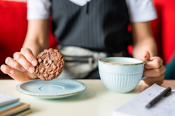 Woman eating a cookie with coffee