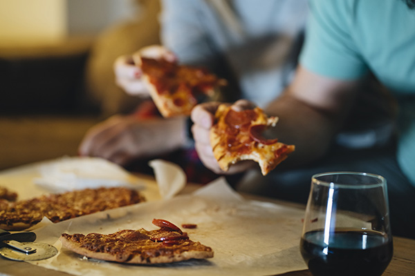 Couple eating pizza on the sofa in their living room