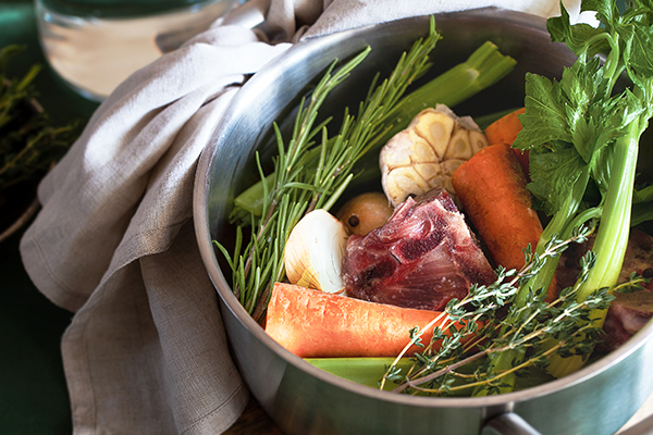 Ingredients for cooking bone broth in pot.