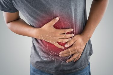 Close up of a man holding his stomach with the outline of a large intestine drawn on it and glowing in red - idea of gastrointestinal issues like ulcerative colitis