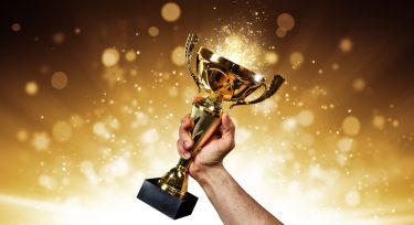 an holding up a gold trophy cup with abstract shiny background