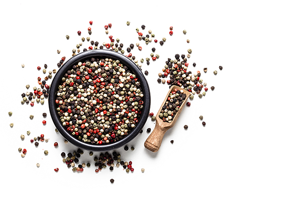 Top view of a black bowl filled with multicolored peppercorns