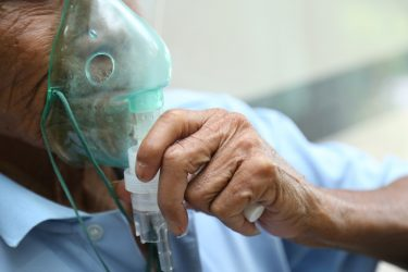 Elderly male patient wearing an oxygen mask - idea of respiratory distress/inhaled drug delivery